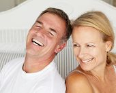 picture of married couple  - Happy couple sitting back to back on bed - JPG