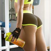 Active Sexy Woman In A Sport Green Clothes Stands At A Sports Gym Equipment. Sports Nutrition. Amino poster