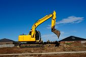 stock photo of land-mass  - Yellow excavator during earthmoving works outdoors at construction site - JPG