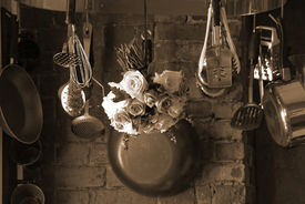 stock photo of kitchen utensils  - sepia toned image of country kitchen with roses hanging from the pot rack drying - JPG