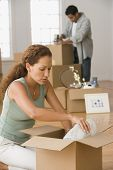 Hispanic couple packing moving boxes