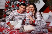 Family In Pajamas Sits On A Bed Near The Christmas Tree Mom, Dad And Toddler, Idyll, Christmas Celeb poster