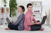 picture of concubine  - Couple sitting back to back and working on their laptops - JPG