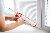 Construction Worker Use Gun Silicone Tube For Repairing And Installing Window In House poster