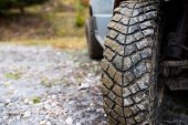 Used Cracked Off Road Tire On Off Road Vehicle , Forest Road Close Up Shot With Copy Space. poster