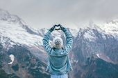 Back view of young traveler girl in gloves and hat standing over snowy mountain peaks and making sha poster