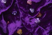 Glass Colored Hearts On A Purple Velvet Background. poster