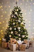 Christmas Tree And Heap Of Gift Boxes Over White Brick Wall With Yellow Lights poster