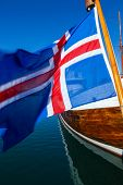 Icelandic flag and traditional wooden boat, Reykjavik Harbor, Iceland poster