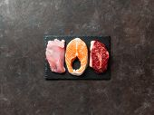 Raw Turkey Breast Fillet, Salmon Steak And Beef Ribeye Steak On Black Slate Board Over Dark Backgrou poster