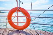 Orange Lifebuoy With Rope On A Wooden Pier Near Sea. Close Up Of Lifebuoy On Wooden Pier At The Beac poster