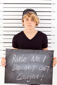image of mug shot  - teen boy holding a blackboard criminal mug shot - JPG