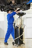 auto mechanic technician replacing and changing motor oil in automobile engine at maintenance repair