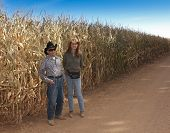 A Farmer And His Daughter Stand By A Cornfield