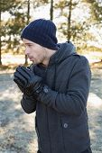 pic of shivering  - Young man in warm clothing shivering while having a walk in forest on a winter day - JPG