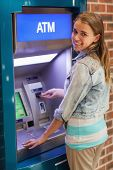 Pretty smiling student withdrawing cash at an ATM
