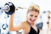 stock photo of lifting weight  - Woman in gym lifting weights - JPG