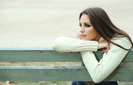 stock photo of sitting a bench  - Young lonely woman on bench in park - JPG