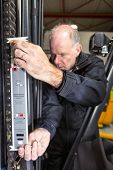 Man measuring the chain of a forklift