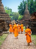 Novice Buddhist Monks Walking Among Ruins in Sukhothai, Thailand