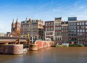 Amsterdam, Netherlands - March 19, 2014: Colorful Building Facades And Bridge With Walking People. D