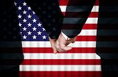 picture of same sex marriage  - Two gay men stand hand in hand before a marriage altar featuring an overlay of the flag of the United States of America - JPG