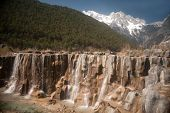 image of jade blue  - White Water River Waterfall Under The Mountain Range With Nobody In Lijiang Near Jade Dragon Snow Mountain in Yunnan province - JPG