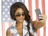 Young woman taking a SELFIE portrait of herself for  social networking with the American Flag behind