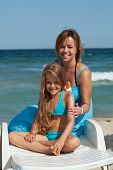 Woman and little girl using sunscreen cream - sitting on a beach chair
