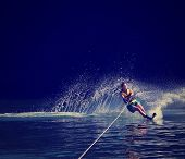 picture of ski boat  -  a young woman water skiing on a lake done with a retro vintage instagram filter  - JPG