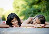 pic of hopscotch  - Two sisters laughing and playing with chalks on pavement in green sunny park - JPG