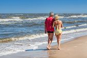 stock photo of stroll  - Mature couple strolling together at sandy coastline - JPG