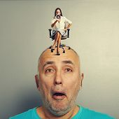 shocked man with small displeased woman on his head over grey background
