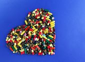 Heart of pills on blue background