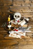 Conceptual photo of love magic. Composition with skull, voodoo doll, dried herbs and candle on  dark