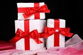 Beautiful gifts with red ribbons on dark background