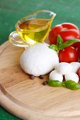 Composition with tasty mozzarella cheese balls, basil and red tomatoes, olive oil on cutting board,