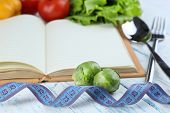 Book with cutlery,measuring tape and vegetables on wooden background
