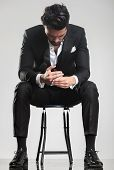 foto of studio  - Elegant young man in tuxedo looking down while sitting on a stool - JPG
