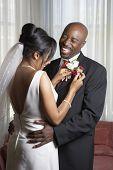 picture of lapel  - Bride pinning flowers onto groom - JPG