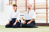 image of aikido  - Man and woman at Aikido training in martial arts school  - JPG