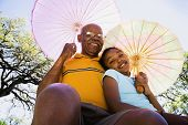 picture of granddaughter  - African American grandfather and granddaughter with parasols - JPG