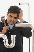 stock photo of plumber  - Confused plumber working on pipes - JPG