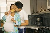 stock photo of pajamas  - Pregnant couple in pajamas in kitchen - JPG