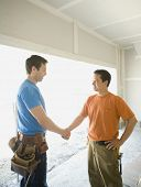 stock photo of friendship belt  - Male carpenters shaking hands inside construction site - JPG