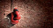 stock photo of boxing  - Pair of red boxing gloves hanging on wall - JPG