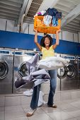 stock photo of laundromat  - Young woman screaming while carrying overloaded laundry basket at laundromat - JPG