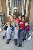 image of nuclear family  - African family sitting on front steps - JPG