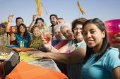 stock photo of niece  - Large Hispanic family toasting at party outdoors - JPG