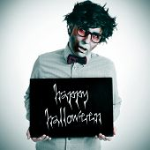 image of zombie  - a hipster zombie showing a black signboard with the text happy halloween written in it - JPG
